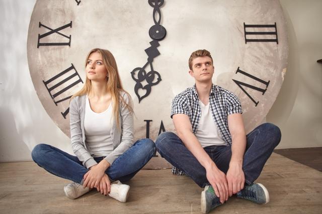 時計の前に座るカップル