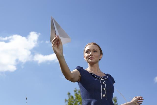 青空のもと紙飛行機を飛ばす女性