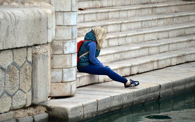 階段で一人たたずむ女性